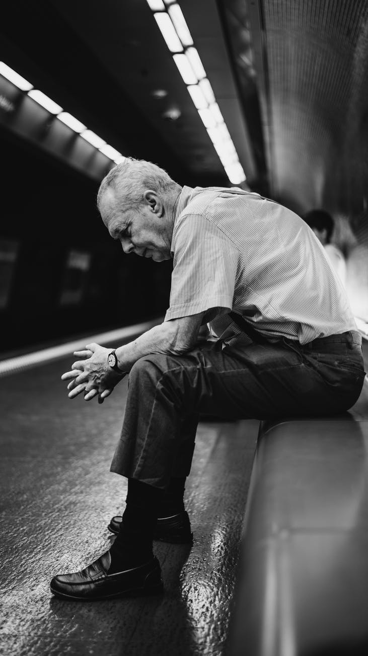 grayscale photography of sitting man
