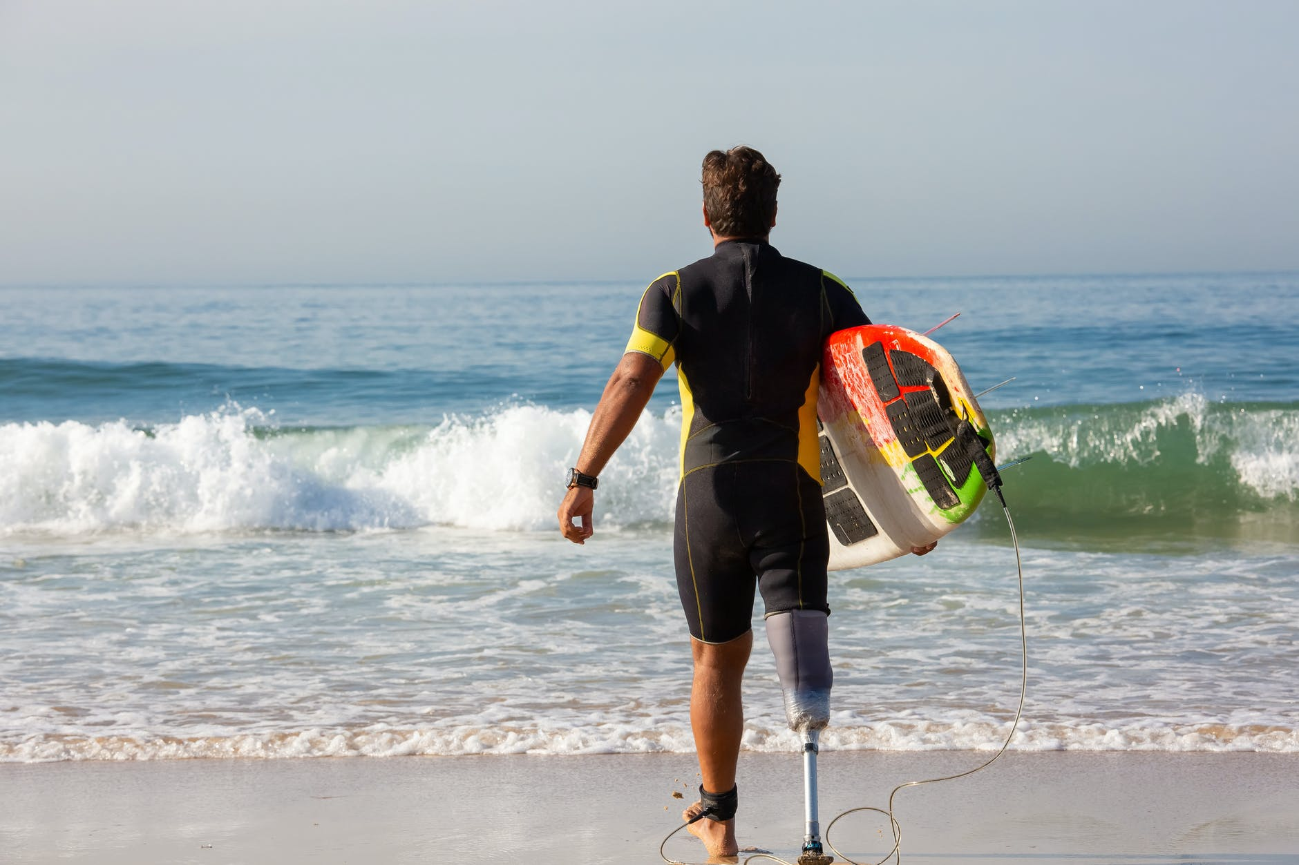 unrecognizable male surfer amputee with surfboard walking towards sea