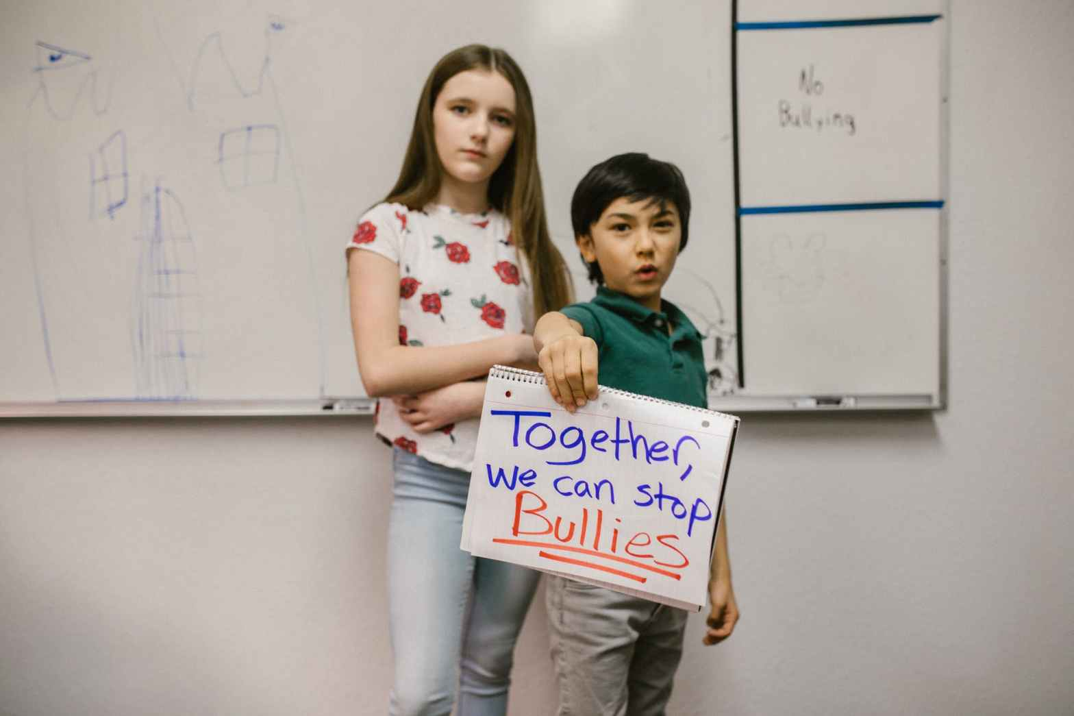 two students showing a message against bullying