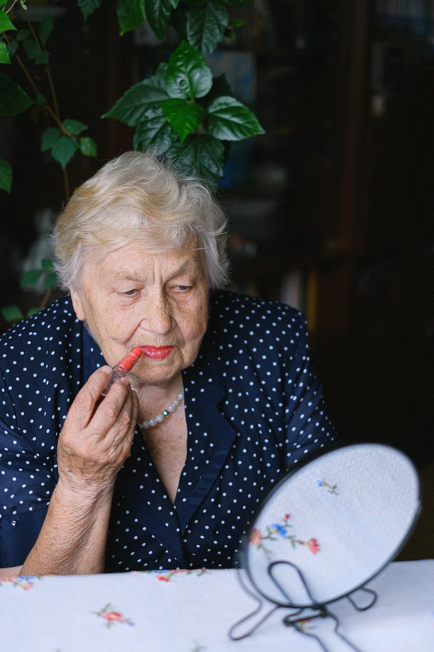 old woman doing makeup in room