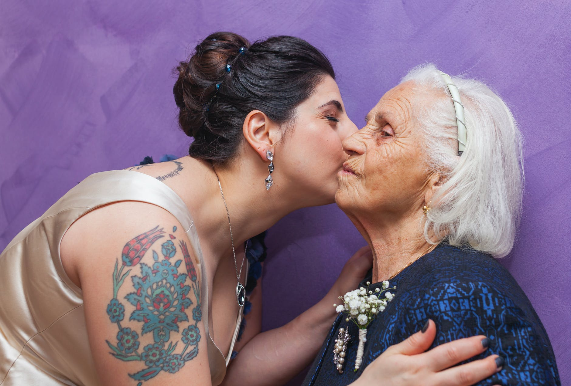 woman kissing woman with boutonniere on chest