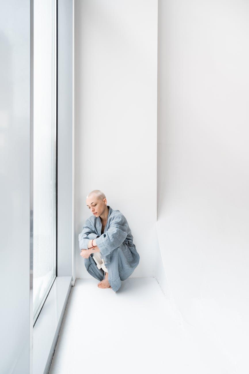 depressed patient against window in light hospital
