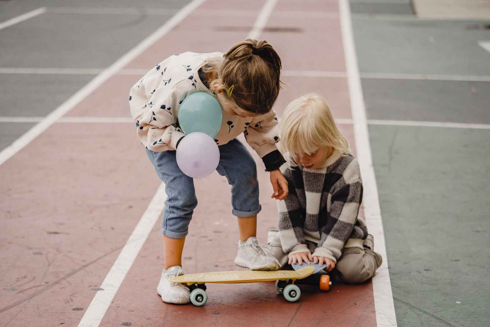 anonymous girlfriends playing with balloons and skateboard on sports ground