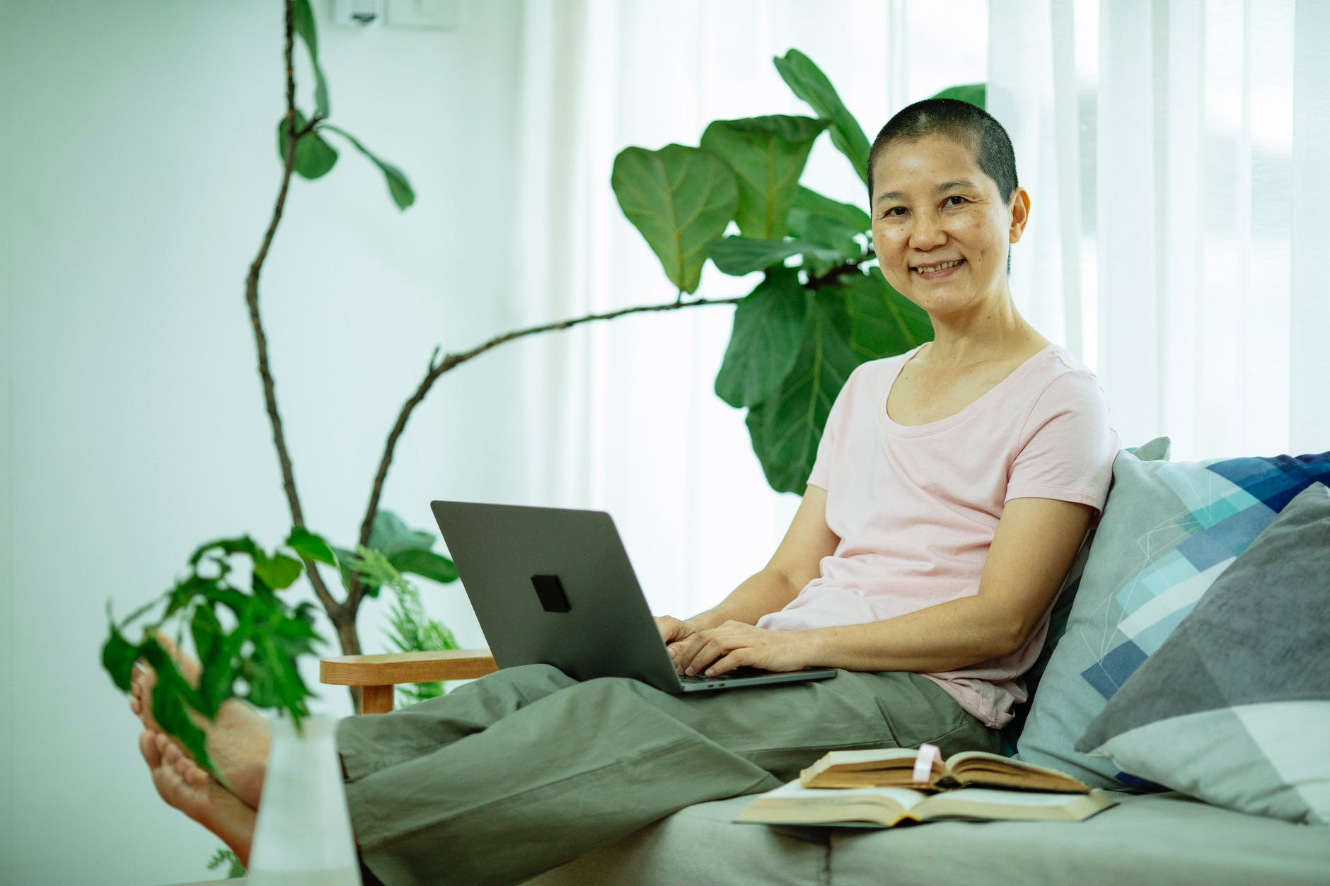 happy asian lady using netbook on couch in living room