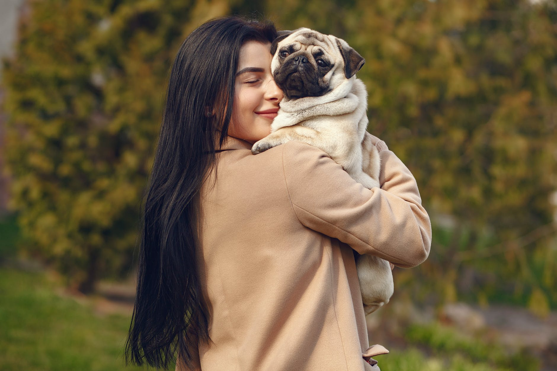 happy woman with pug on hands
