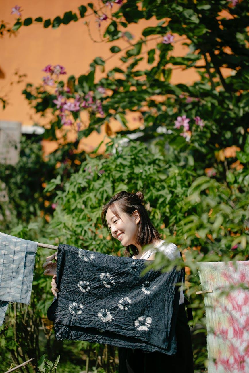 joyful asian woman near rope with painted fabrics