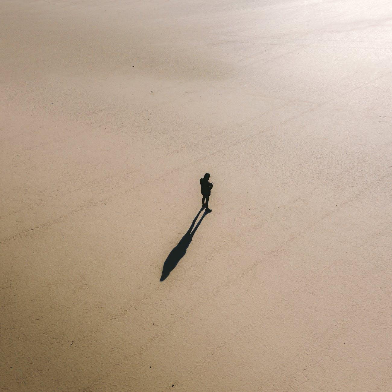 silhouette of man standing on sandy terrain