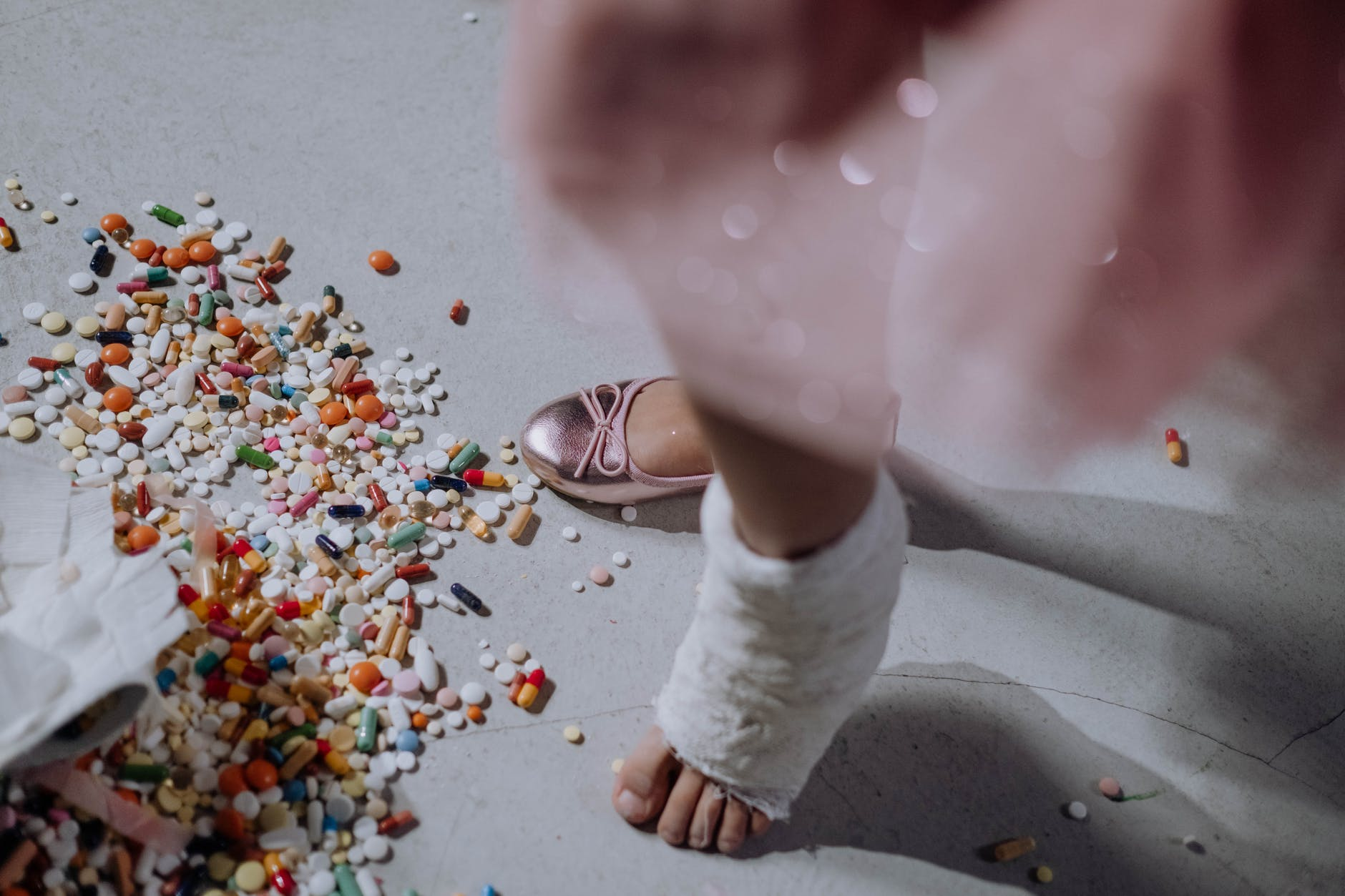 person in white pants and brown leather shoes standing on gray concrete floor with pink petals