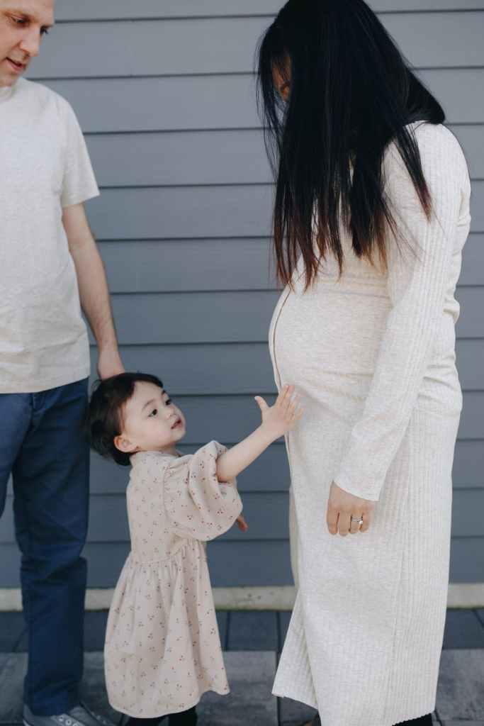 little girl holding her mom s tummy