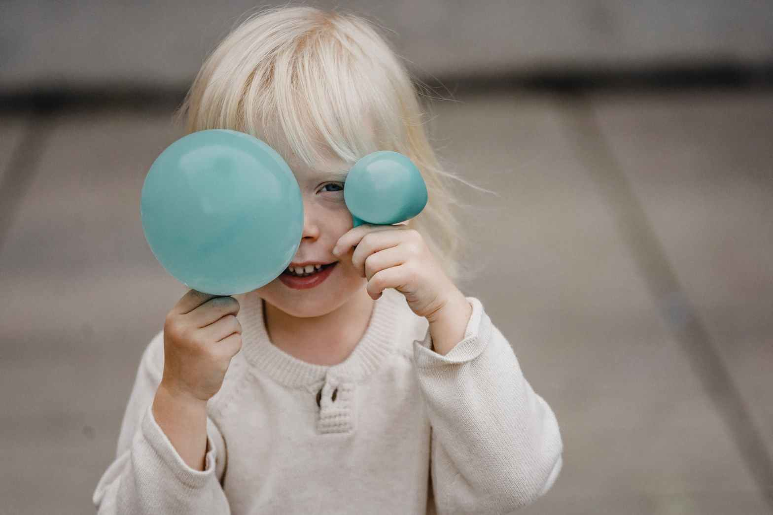 smiling little girl covering face with balloons on street