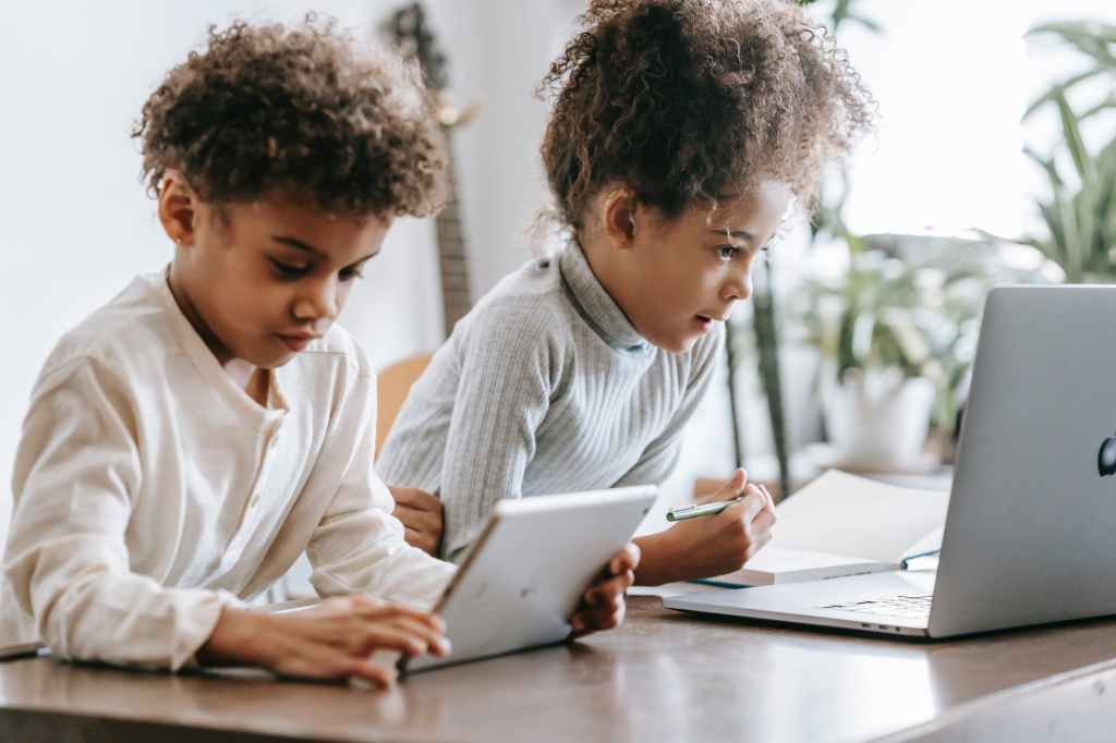 concentrated black children using laptop and tablet at home