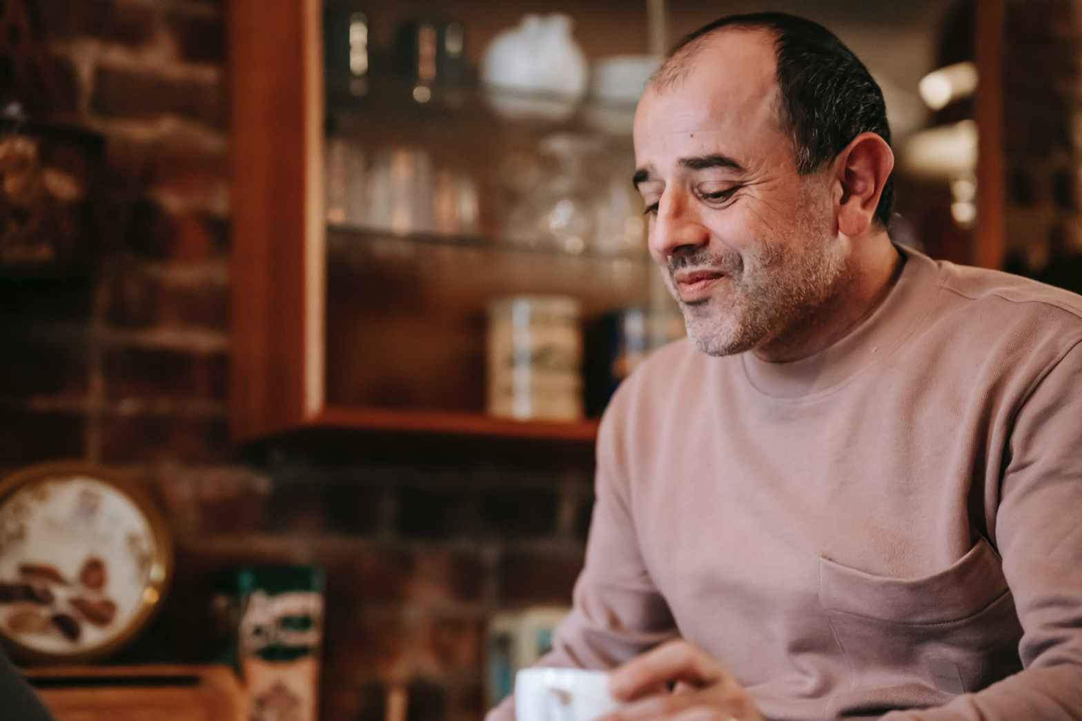 delighted ethnic man drinking hot beverage at home in morning