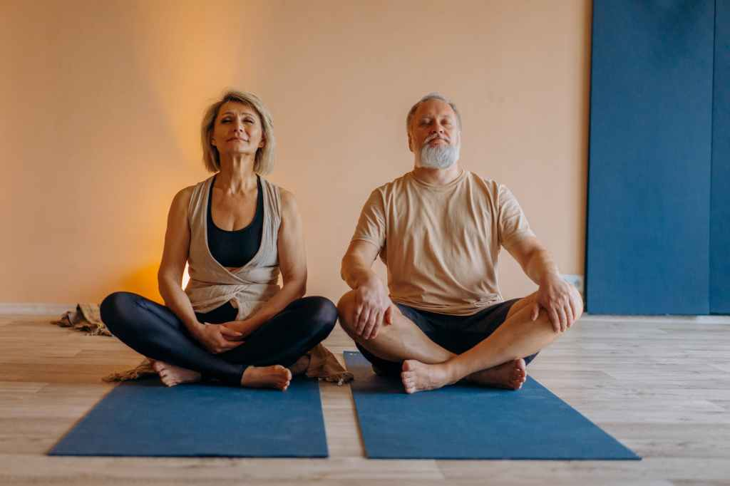 man and woman sitting on blue yoga mat