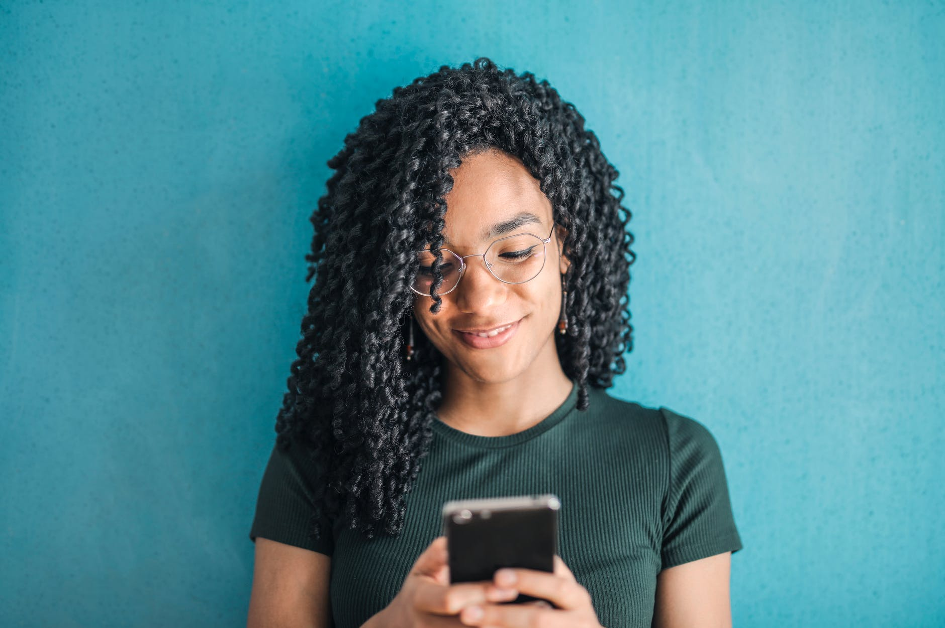 portrait photo of smiling woman in black t shirt and glasses using her smartphone